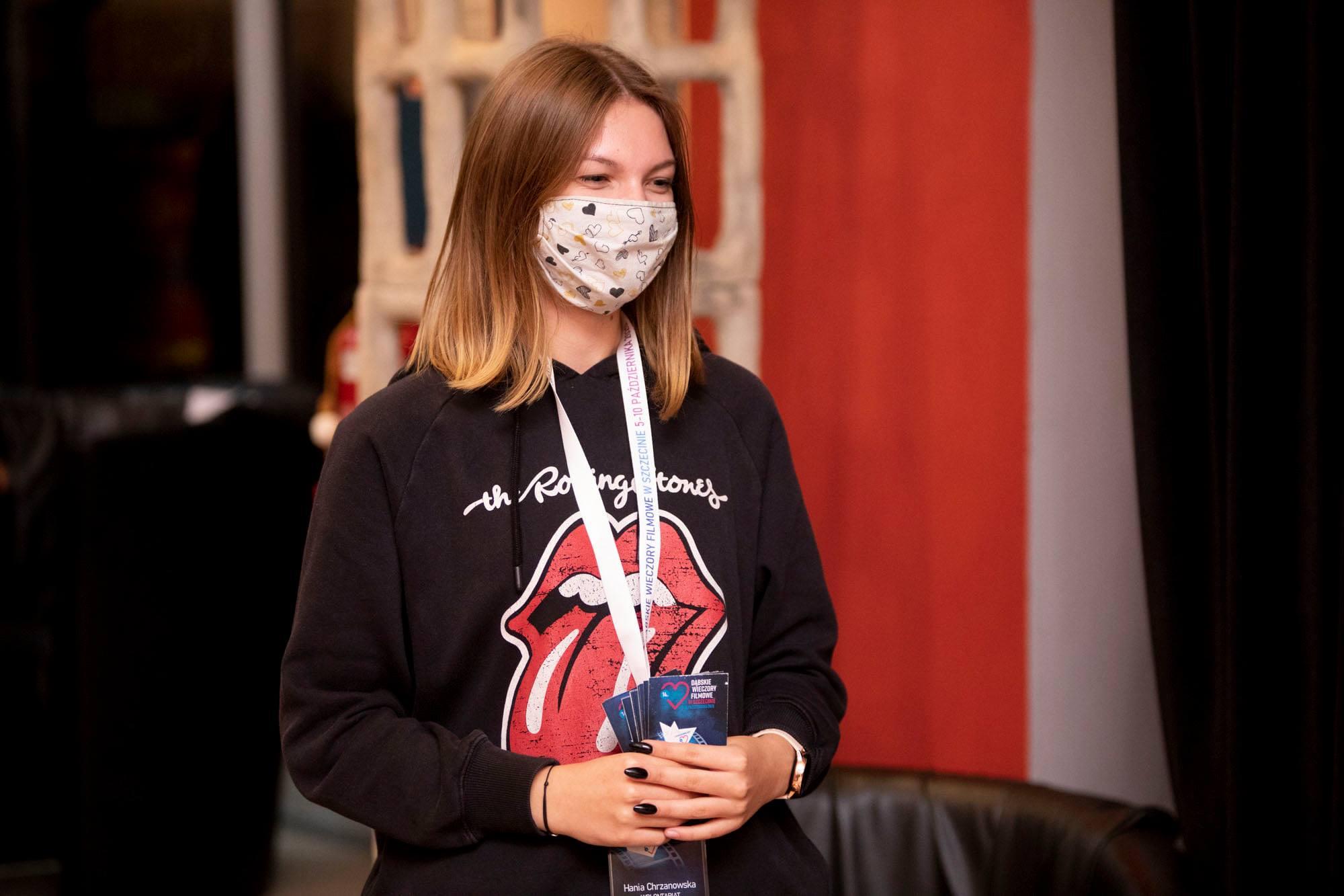 Młoda wolontariuszka z maseczce na twarzy rozdaje ulotki DWF