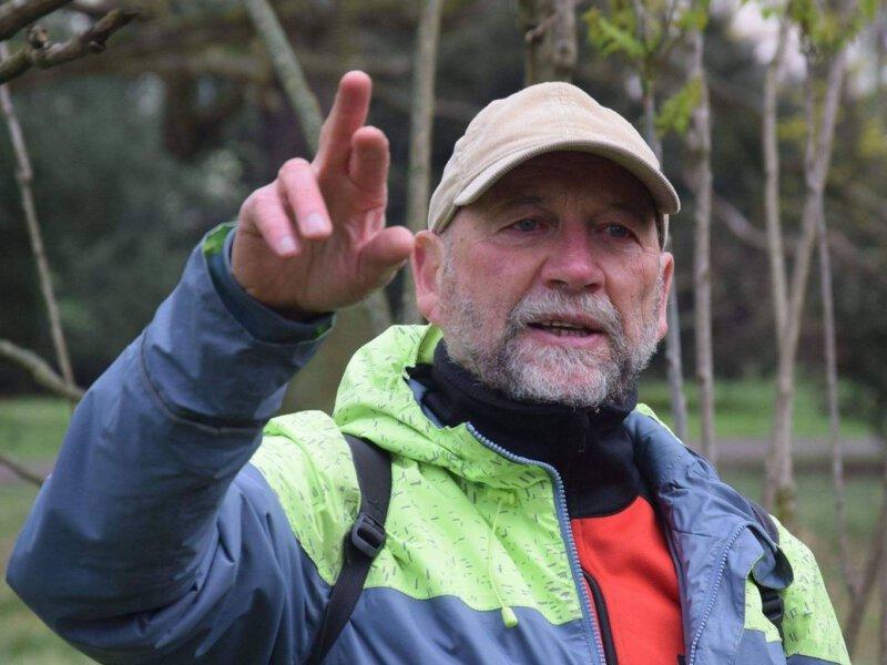 Paweł Madejski na tle drzew wskazuje coś poza kadrem