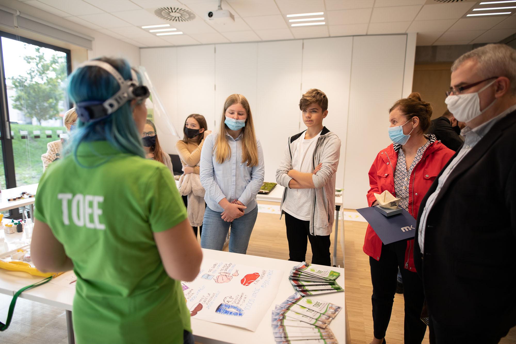 Pracownica TOEE rozmawia z grupką młodzieży podczas warsztatów ekologicznych w ramach 14. Dąbskich Wieczorów Filmowych